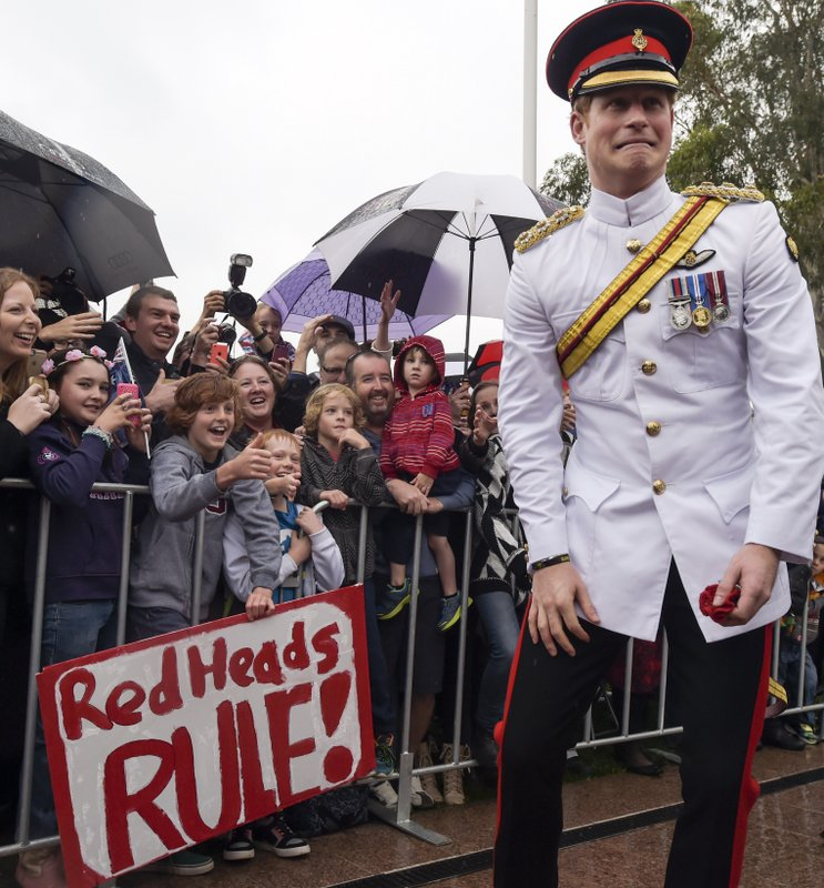 FILE - In this Monday, April 6, 2015 file photo, Britain's Prince Harry, right, reacts after shaking hands with kids holding up a sign reading