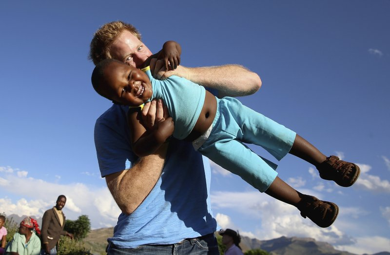 FILE - In this file photo taken on Dec. 6 2014, Britain's Prince Harry swings young three year old orphan boy  Lerato in this photograph taken with the help of a three year old blind girl called Karabo during a visit to Phelisanong Children's Home in Maseru, Lesotho. (AP Photo / Chris Jackson, Pool, File)