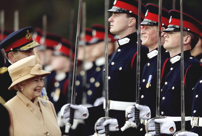 FILE - In this Wednesday, April 12, 2006 file photo, Britain's Prince Harry, second from right, grins and his grandmother Queen Elizabeth II smiles, as she inspects the Sovereign's Parade at the Royal Military Academy in Sandhurst, England. (Dylan Martinez, Pool Photo via AP, File)