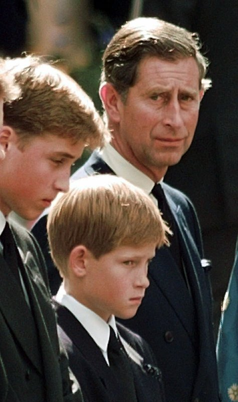 FILE - In this Saturday, Sept. 6, 1997 file photo, Britain's Prince Charles, the Prince of Wales and his sons Prince William, left and Prince Harry wait for the coffin of Princess Diana to be loaded into a hearse outside of Westminster Abbey, in London. (John Gaps III, Pool Photo via AP, File)