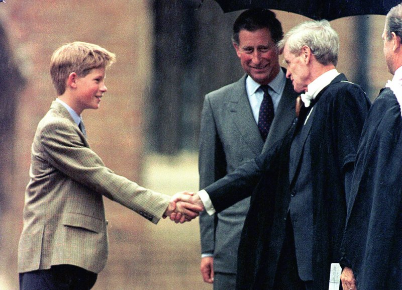 FILE - In this Wednesday, Sept. 2, 1998 file photo, Britain's Prince Harry meets Headmaster John Lewis, right, as Prince Charles looks on, after his arrival at the prestigious Eton college, in Eton, England. (Pool Photo via AP, File)