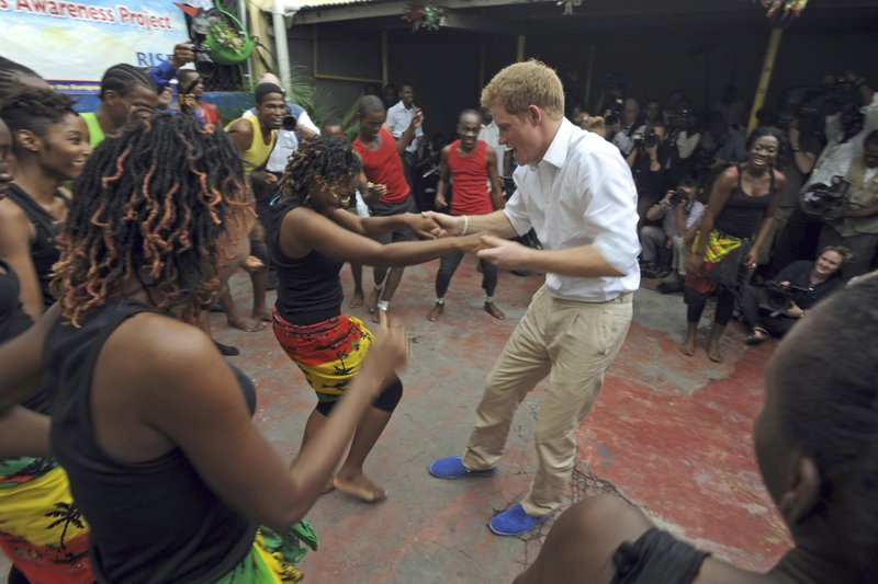 FILE - In this Tuesday, March 6, 2012 file photo, Britain's Prince Harry dances with a girl during a visit to the non-governmental organization RISE (Reaching Individuals through Skills and Education) in Kingston, Jamaica. (AP Photo/Collin Reid, File)