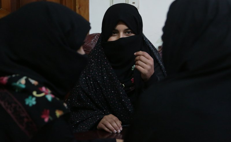 In this Monday, Feb. 18, 2019, photo, Alissa, who faced domestic violence, center, speaks during an interview with the Associated Press at a women's shelter office in Herat, Afghanistan. (AP Photo/Rahmat Gul)