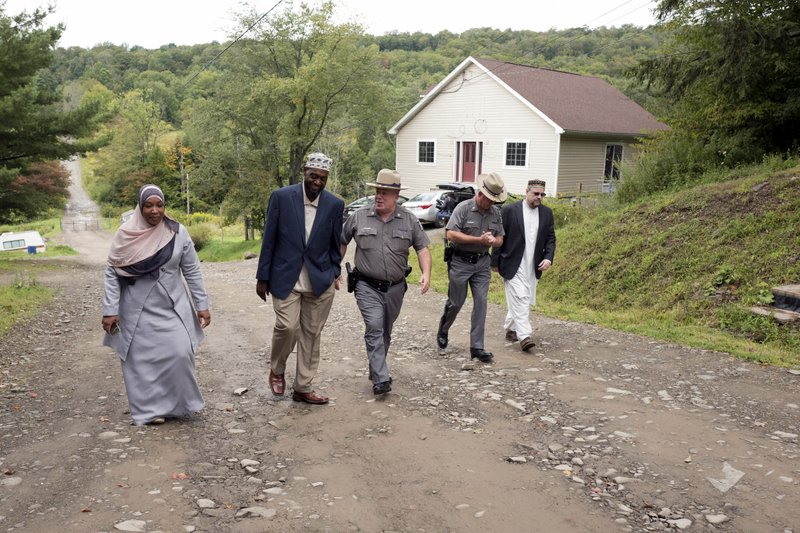 FILE - In this Sept. 7, 2017 file photo, Tahirah Clark, left, and Faruq Baqi walk with New York State Police Capt. (AP Photo/Mark Lennihan)