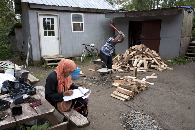 FILE - In this Sept. 7, 2017 file photo, a girl studies for school while a man chops wood in the Muslim enclave of Islamberg in Delaware County, N. (AP Photo/Mark Lennihan)