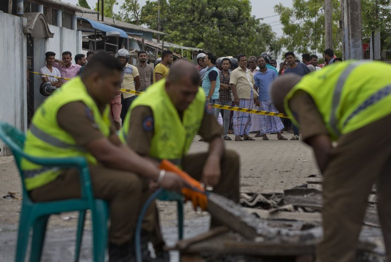 Police officers collect evidence from a site of a gun battle between troops and suspected Islamist militants as neighbors gather to watch in Kalmunai, Sri Lanka, Sunday, April 28, 2019. (AP Photo/Gemunu Amarasinghe)