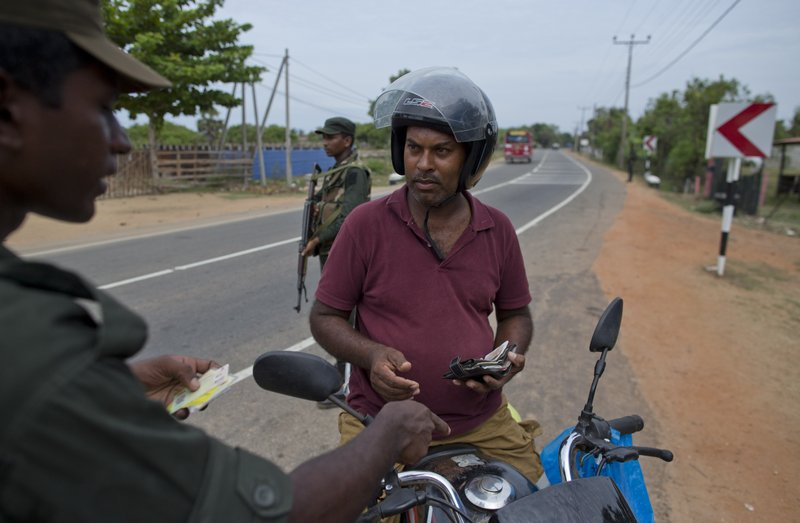 An army officer checks the identity of a man on a motor bike at a roadside checkpoint in Kalmunai, Sri Lanka, Sunday, April 28, 2019. (AP Photo/Gemunu Amarasinghe)