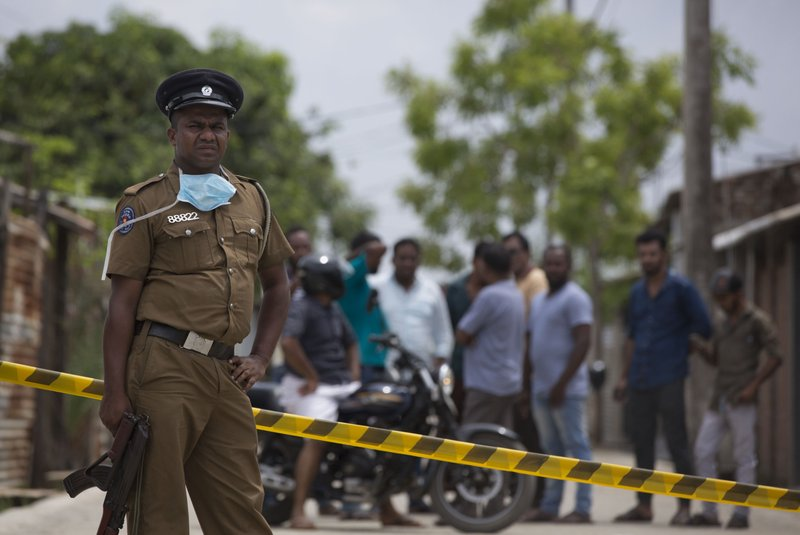 A police officer stand guards at a site of a gun battle between troops and suspected Islamist militants as neighbors gather to watch in Kalmunai, Sri Lanka, Sunday, April 28, 2019. (AP Photo/Gemunu Amarasinghe)