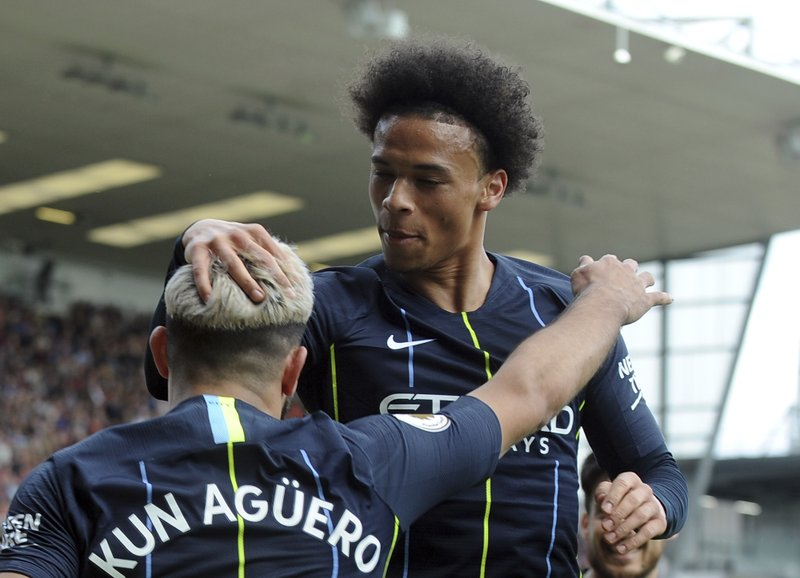 Manchester City's Sergio Aguero, left, celebrates with Manchester City's Leroy Sane after scoring his side's opening goal during the English Premier League soccer match between Burnley and Manchester City at Turf Moor in Burnley, England, Sunday, April 28, 2019. (AP Photo/Rui Vieira)