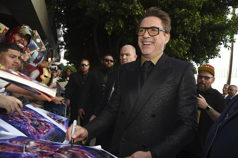 Robert Downey Jr. signs autographs as he arrives at the premiere of