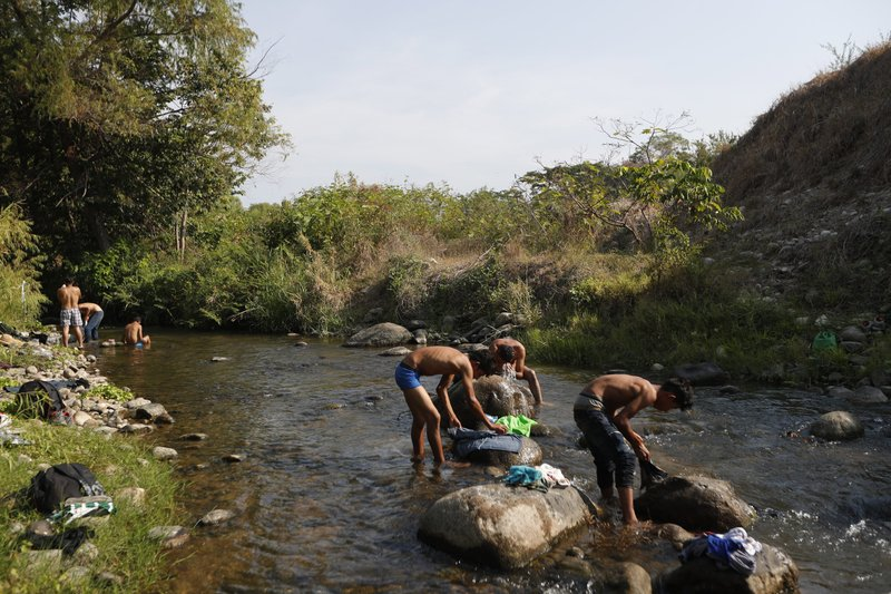 Central American migrants traveling in a caravan headed to the U.S. border wash clothes and take baths in a river on a rest day near Mapastepec in Chiapas state, Mexico, Sunday, April 21, 2019. (AP Photo/Moises Castillo)