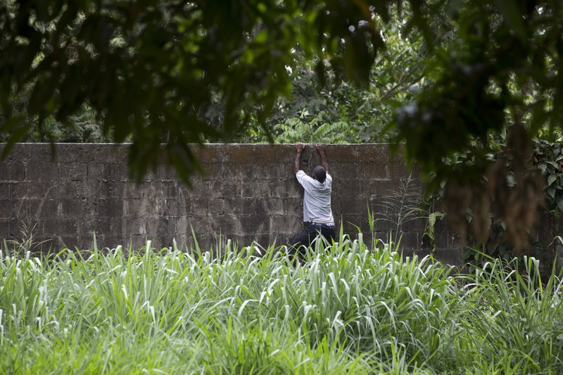 A migrant climbs a wall to return to a migrant shelter in