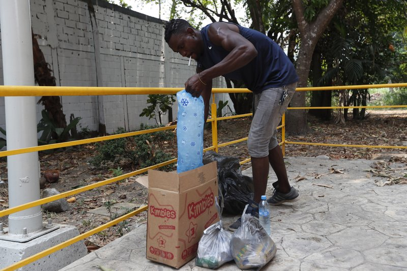 Haiti migrant Ivan Pierre, 25, puts ice on food he bought for his family staying at a shelter inside