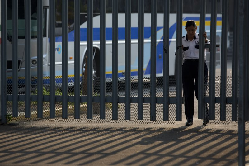 A security guard closes a gate at an immigration detention center in Tapachula, Chiapas state, Mexico, Saturday, April 27, 2019. (AP Photo/Moises Castillo)