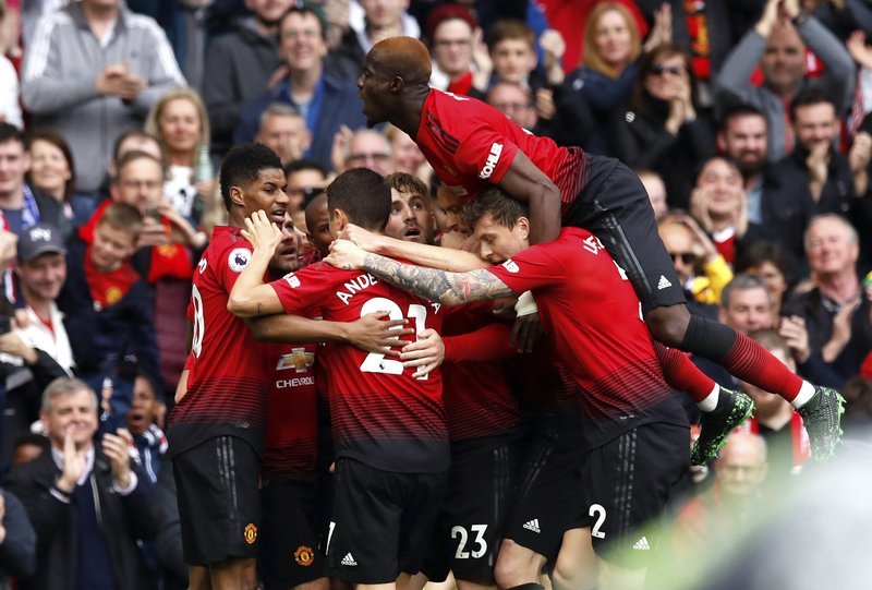 Manchester United's Juan Mata, center obscured, celebrates scoring his side's first goal of the game with teammates during their English Premier League soccer match against Chelsea at Old Trafford, Manchester, England, Sunday, April 28, 2019. (Martin Rickett/PA via AP)