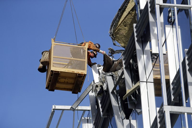 Workers suspended in a basket reach out toward debris from a building damaged when the crane atop it collapsed a day earlier, Sunday, April 28, 2019, in Seattle. (AP Photo/Elaine Thompson)