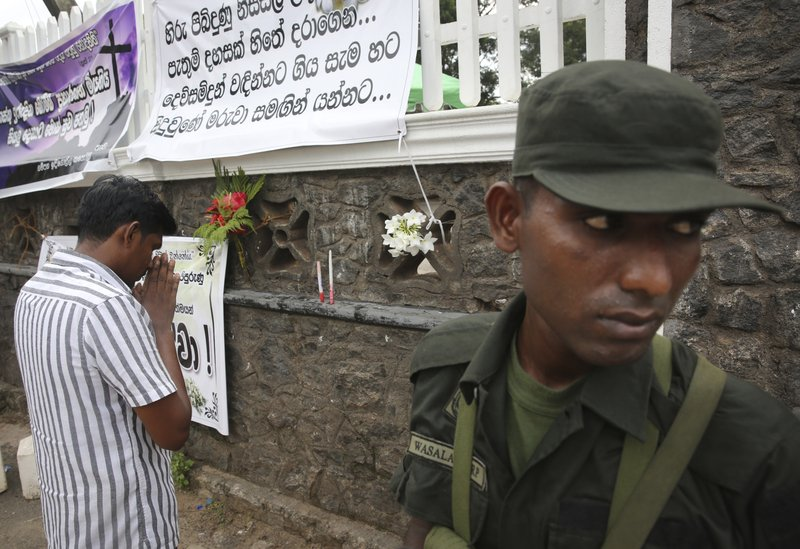 A relative of an Easter Sunday bomb blast victim prays after placing the flowers on the wall of St. Sebastian's Church in Negombo, north of Colombo, Sri Lanka, Sunday, April 28, 2019. (AP Photo/Manish Swarup)