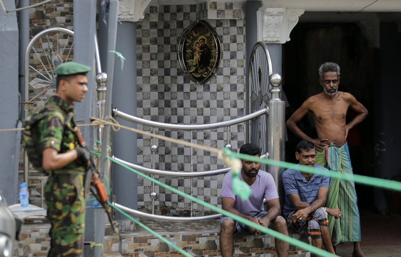 A Sri Lankan police commando secure the area of the exploded St. Anthony's Church on Easter Sunday attacks as people wait next to a small roadside in Colombo, Sri Lanka, Sunday, April 28, 2019. (AP Photo/Eranga Jayawardena)