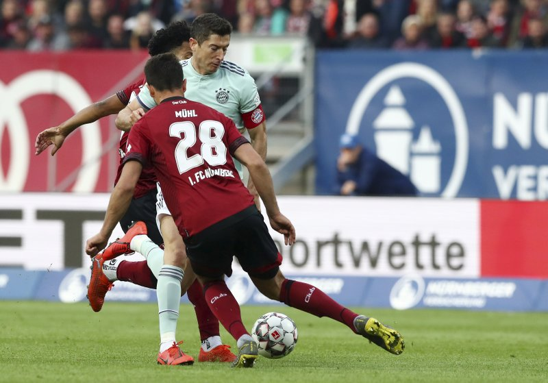 Bayern's Robert Lewandowski, right, tries to dribble past Nuremberg's Lukas Muehl, bottom left, and Nuremberg's Matheus Pereira during the German Bundesliga soccer match between 1. (AP Photo/Matthias Schrader)