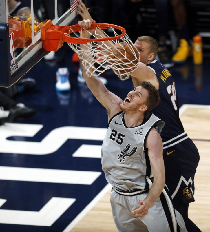 San Antonio Spurs center Jakob Poeltl, front, dunks the ball as Denver Nuggets forward Mason Plumlee defends in the second half of Game 7 of an NBA basketball first-round playoff series, Saturday, April 27, 2019, in Denver. (AP Photo/David Zalubowski)