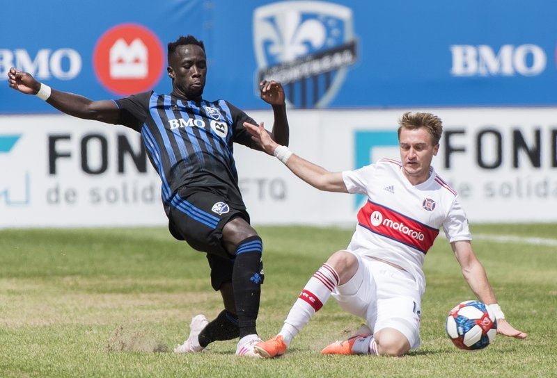 Montreal Impact's Bacary Sagna, left, challenges Chicago Fire's Djordje Mihailovic during second-half MLS soccer match action in Montreal, Sunday, April 28, 2019. (Graham Hughes/The Canadian Press via AP)