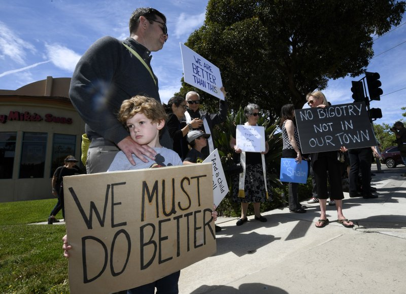 Kyle Fox, 4, and his father Brady Fox hold a sign at a vigil held to support the victims of Chabad of Poway synagogue shooting, Sunday, April 28, 2019, in Poway, Calif. (AP Photo/Denis Poroy)