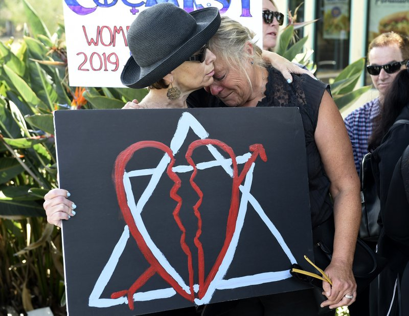 Leslie Gollub, left, and Gretchen Gordon hug at a vigil held to support the victims of Saturday's shooting at Chabad of Poway synagogue, Sunday, April 28, 2019, in Poway, Calif. (AP Photo/Denis Poroy)