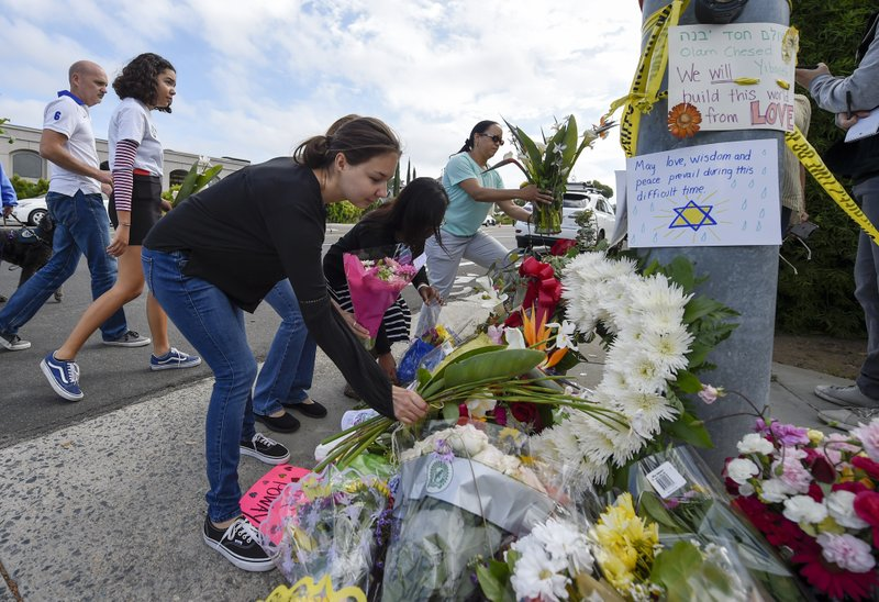 A group of Poway residents bring flowers and cards to a memorial outside of the Chabad of Poway synagogue, Sunday, April 28, 2019, in Poway, Calif. (AP Photo/Denis Poroy) (AP Photo/Denis Poroy)