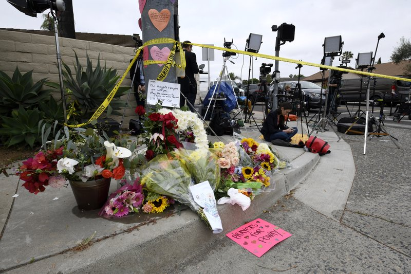 Flowers and signs sit at a memorial across the street from the Chabad of Poway synagogue, Sunday, April 28, 2019, in Poway, Calif. (AP Photo/Denis Poroy)