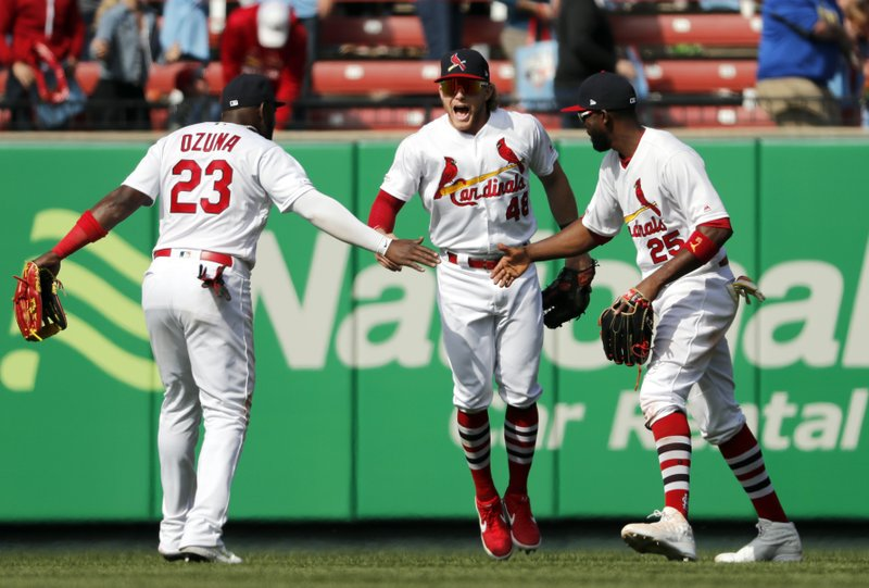St. Louis Cardinals' Marcell Ozuna (23), Harrison Bader (48) and Dexter Fowler (25) celebrate following a victory over the Cincinnati Reds in a baseball game Sunday, April 28, 2019, in St. (AP Photo/Jeff Roberson)
