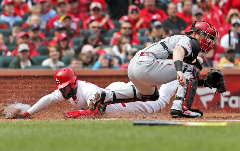 St. Louis Cardinals' Marcell Ozuna, left, scores past Cincinnati Reds catcher Tucker Barnhart during the fourth inning of a baseball game Sunday, April 28, 2019, in St. (AP Photo/Jeff Roberson)