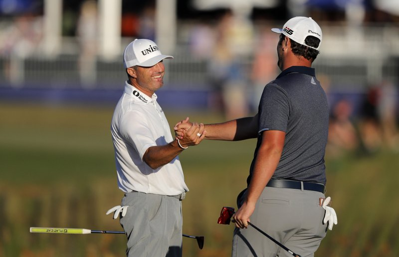 John Rahm, right, celebrates with teammate Ryan Palmer after sinking a birdie putt on the 18th green to tie the lead on their last shot for the day during the third round of the PGA Zurich Classic golf tournament at TPC Louisiana in Avondale, La. (AP Photo/Gerald Herbert)