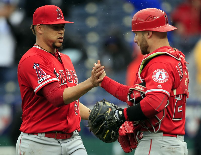 Los Angeles Angels relief pitcher Hansel Robles, left, celebrates with catcher Jonathan Lucroy, right, following a baseball game against the Kansas City Royals at Kauffman Stadium in Kansas City, Mo. (AP Photo/Orlin Wagner)