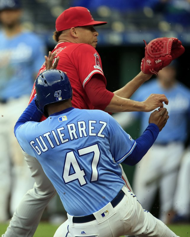 Kansas City Royals' Kelvin Gutierrez (47) scores on a wild pitch while Los Angeles Angels pitcher Hansel Robles, top, covers home plate during the ninth inning of a baseball game at Kauffman Stadium in Kansas City, Mo. (AP Photo/Orlin Wagner)