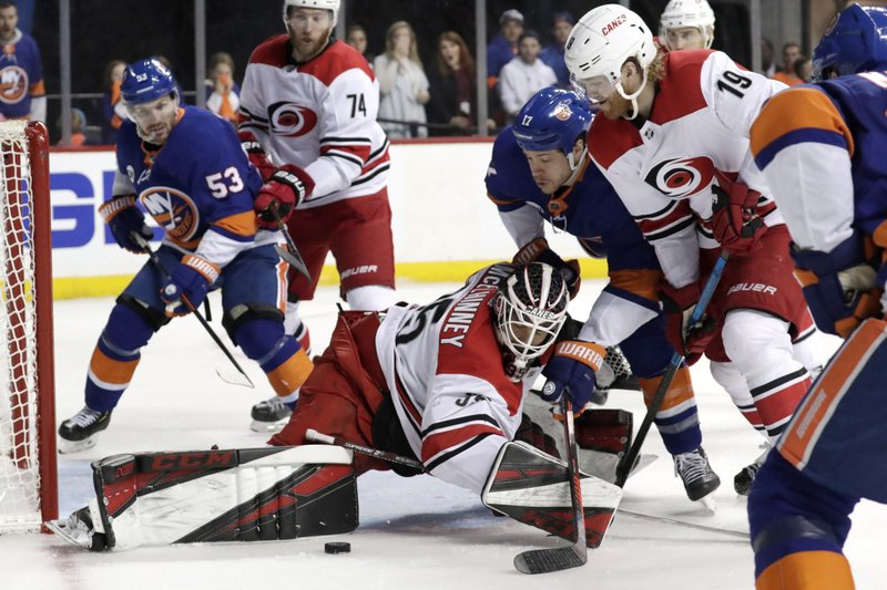 Carolina Hurricanes goaltender Curtis McElhinney (35) makes a save as New York Islanders left wing Matt Martin (17) attacks during the second period of Game 2 of an NHL hockey second-round playoff series, Sunday, April 28, 2019, in New York. (AP Photo/Julio Cortez)