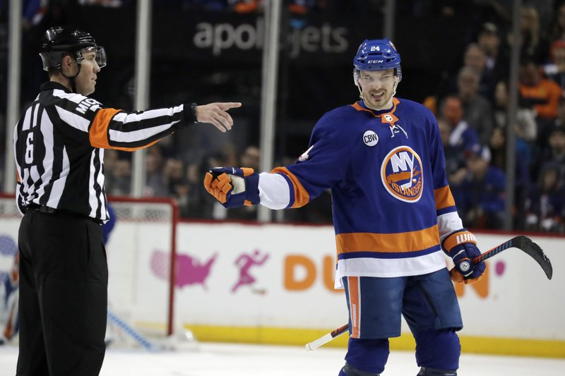 NHL referee Francis Charron (6) sends New York Islanders defenseman Scott Mayfield, right, to the penalty box on a slashing call against the Carolina Hurricanes during the second period of Game 2 of an NHL hockey second-round playoff series, Sunday, April 28, 2019, in New York. (AP Photo/Julio Cortez)