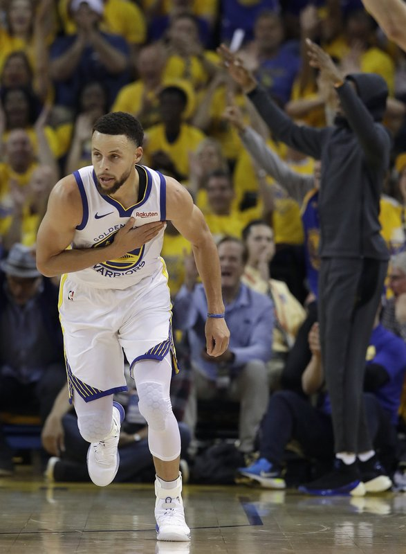 Golden State Warriors guard Stephen Curry reacts after scoring against the Houston Rockets during the first half of Game 1 of a second-round NBA basketball playoff series in Oakland, Calif. (AP Photo/Jeff Chiu)