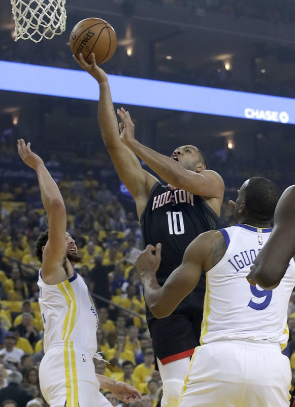 Houston Rockets guard Eric Gordon (10) shoots between Golden State Warriors guards Klay Thompson, left, and Andre Iguodala during the first half of Game 1 of a second-round NBA basketball playoff series in Oakland, Calif. (AP Photo/Jeff Chiu)