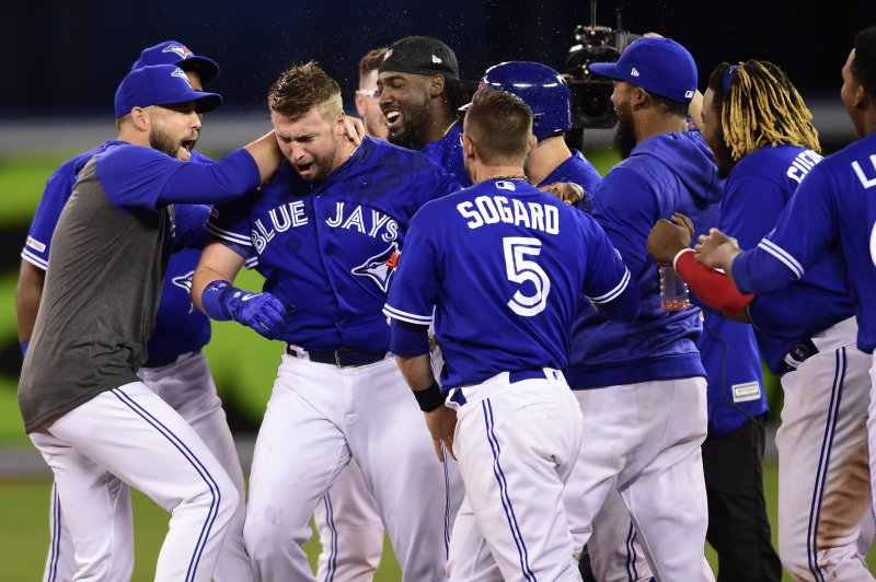 Toronto Blue Jays first baseman Justin Smoak, second left, is mobbed by teammates after driving in the game-winning run against the Oakland Athletics during 11th inning baseball action in Toronto on Sunday, April 28, 2019. (Frank Gunn/The Canadian Press via AP)