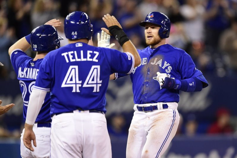 Toronto Blue Jays' Brandon Drury, right, celebrates his game-tying three-run home run with teammates Billy McKinney and Rowdy Tellez during a baseball game against the Oakland Athletics in Toronto, Sunday, April 28, 2019. (Frank Gunn/The Canadian Press via AP)