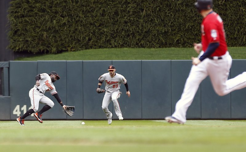 Minnesota Twins' Max Kepler, right, watches as he races to score on a two-run single by Marwin Gonzalez which drops between Baltimore Orioles left fielder Dwight Smith Jr. (AP Photo/Jim Mone)