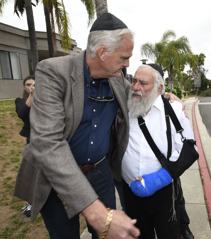 Rabbi Yisroel Goldstein, right, is hugged by Stephen Lee as he arrives for a news conference at the Chabad of Poway synagogue, Sunday, April 28, 2019, in Poway, Calif. (AP Photo/Denis Poroy)
