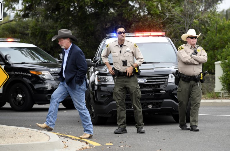 Poway Mayor Steve Vaus, left, walks away after talking to San Diego county sheriff's deputies outside of the Chabad of Poway synagogue, Sunday, April 28, 2019, in Poway, Calif. (AP Photo/Denis Poroy)