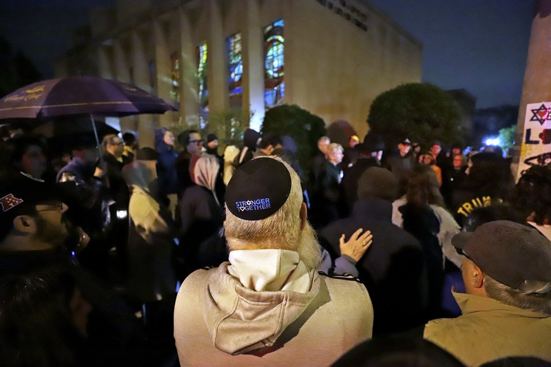 A group gathers outside the Tree of Life Synagogue for a vigil to honor the victims of the Saturday attack on a synagogue in California, Saturday April 27, 2019, in the Squirrel Hill neighborhood of Pittsburgh. (AP Photo/Gene J. Puskar)