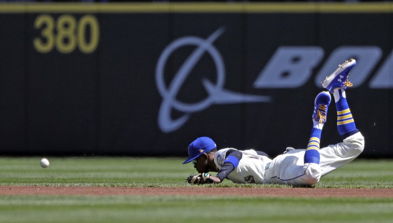 Seattle Mariners second baseman Dee Gordon winds up on the dirt after diving for a single from Texas Rangers' Shin-Soo Choo in the first inning of a baseball game Sunday, April 28, 2019, in Seattle. (AP Photo/Elaine Thompson)