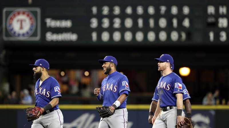 Texas Rangers players smile as they walk off the field in view of the scoreboard after beating the Seattle Mariners in a baseball game, Saturday, April 27, 2019, in Seattle. (AP Photo/Elaine Thompson)