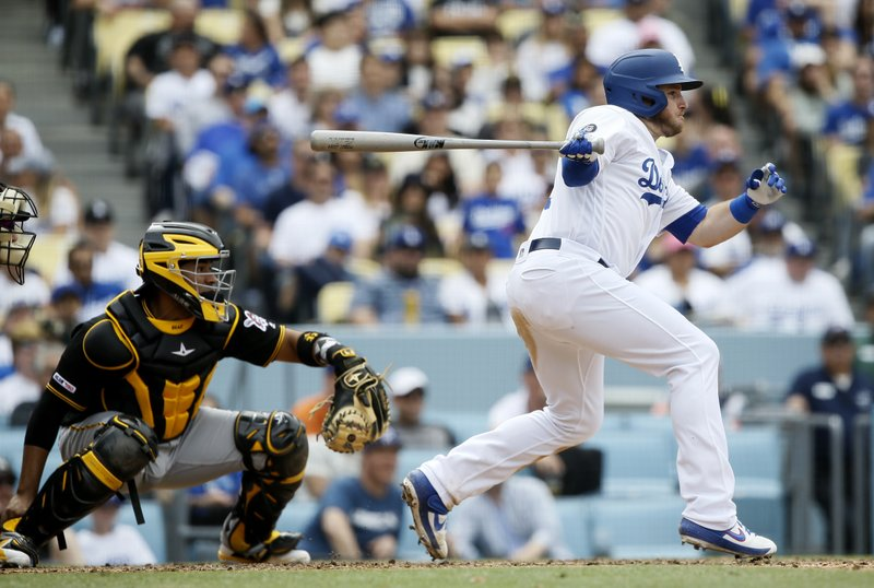 Los Angeles Dodgers' Max Muncy, right, hits an RBI-single with Pittsburgh Pirates catcher Elias Diaz watching during the seventh inning of a baseball game in Los Angeles, Sunday, April 28, 2019. (AP Photo/Alex Gallardo)