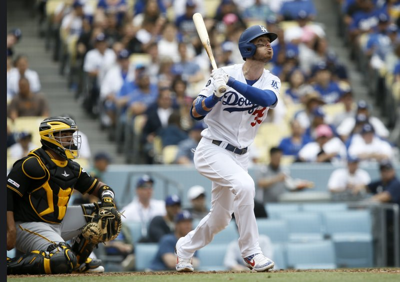 Los Angeles Dodgers' Cody Bellinger, right, hits a solo home run with Pittsburgh Pirates catcher Elias Diaz watching during the fourth inning of a baseball game in Los Angeles, Sunday, April 28, 2019. (AP Photo/Alex Gallardo)