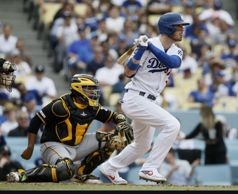Los Angeles Dodgers' Cody Bellinger, right, hits an RBI-single with Pittsburgh Pirates catcher Elias Diaz watching during the seventh inning of a baseball game in Los Angeles, Sunday, April 28, 2019. (AP Photo/Alex Gallardo)