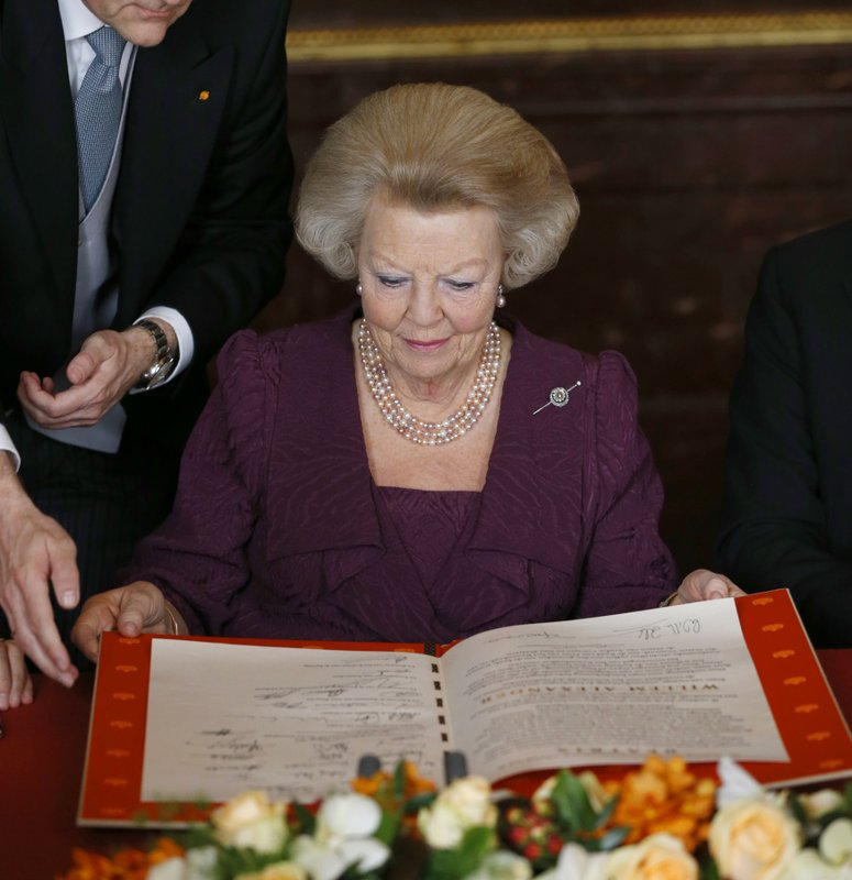 FILE - In this April 30, 2013, file photo, Dutch Queen Beatrix is handed the Act of Abdication which when signed will end her reign as Monarch in the Mozeszaal or Mozes hall of the Royal Palace in Amsterdam, The Netherlands. (Bart Maat/Pool Photo via AP)